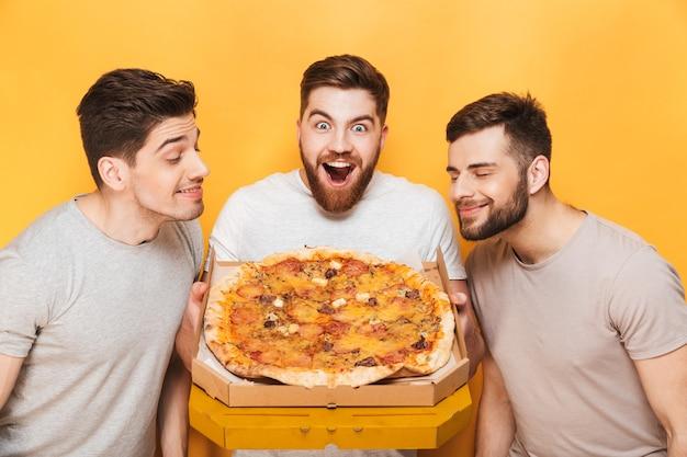 Drie jonge glimlachende mannen die een grote pizza ruiken