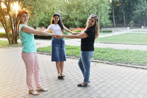 Drie jonge glimlachende vrouwenvrienden die handen houden en de camera bekijken