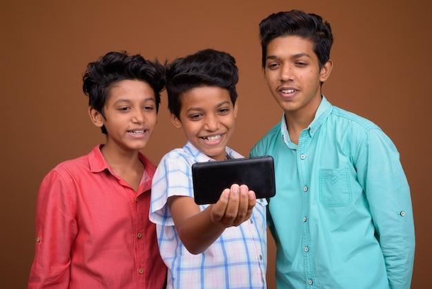 Drie jonge indiase broers samen tegen bruine achtergrond