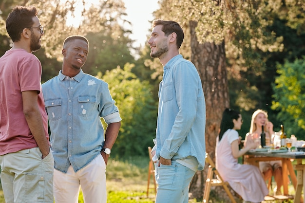 Drie jonge interculturele mannen in vrijetijdskleding staande op groen gazon op zomerdag en praten