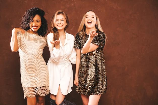 Drie jonge internationale mooie brunette vrouwen in trendy glanzende zomerjurk.