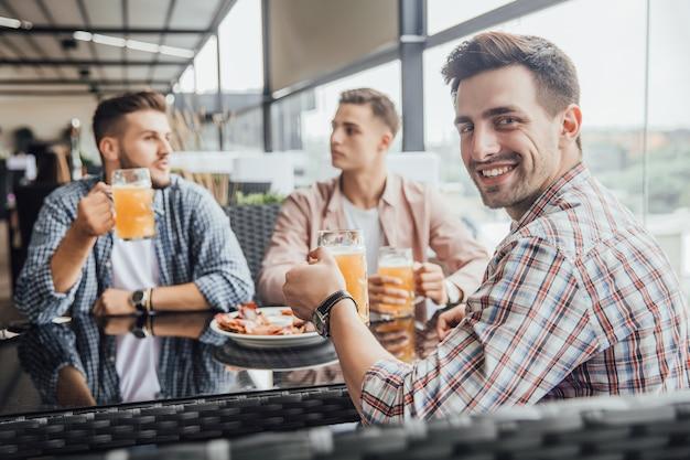 Drie jonge jongens zitten in een café en praten met glazen met bier over hun toekomst