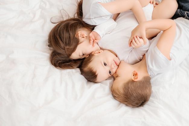 Drie jonge kinderen liggen in bed en knuffelen