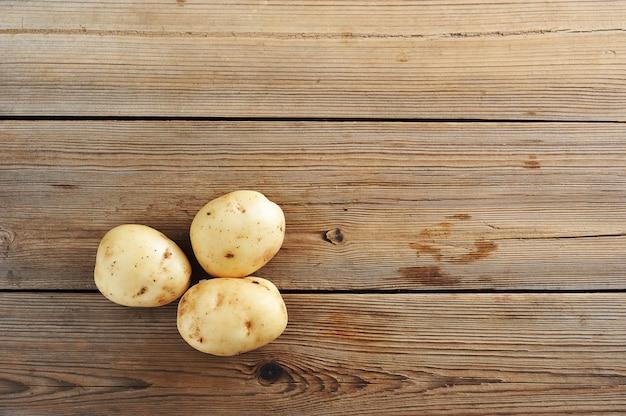 Drie jonge knol ruwe witte aardappels op rustieke houten oppervlakte