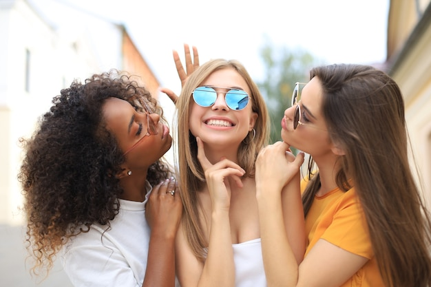 Drie jonge lachende hipster vrouwen in zomer kleding poseren op straat. vrouw positieve gezicht emoties tonen.