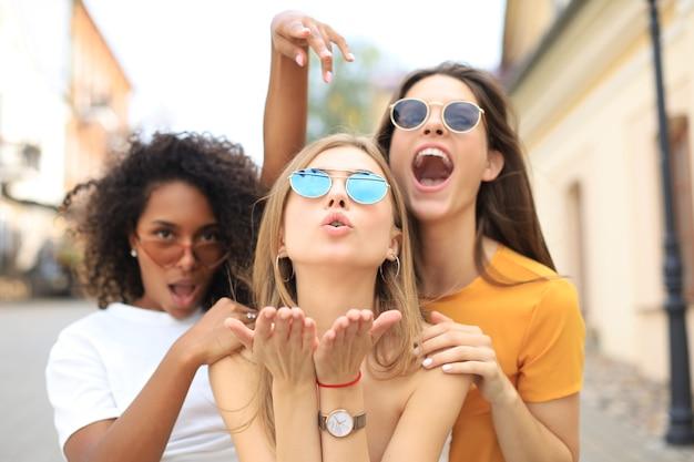 Drie jonge lachende hipster vrouwen in zomer kleding poseren op straat. vrouw positieve gezicht emoties tonen. Premium Foto