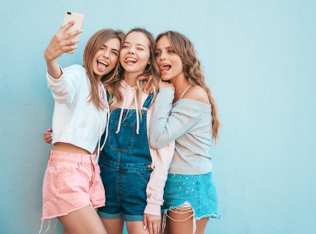 Drie jonge lachende hipster vrouwen in zomerkleren. meisjes nemen selfie zelfportret foto's op smartphone. modellen poseren in de straat in de buurt van muur. vrouwelijke tonen positief gezicht emoties