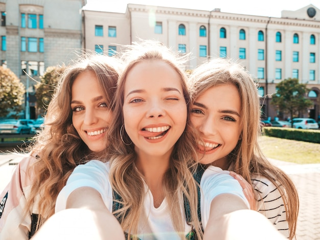 Drie jonge lachende hipster vrouwen in zomerkleren. meisjes nemen selfie zelfportret foto's op smartphone. modellen poseren in de straat. vrouwelijke tonen positief gezicht emoties