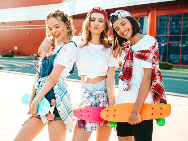Drie jonge lachende mooie meisjes met kleurrijke penny skateboards.