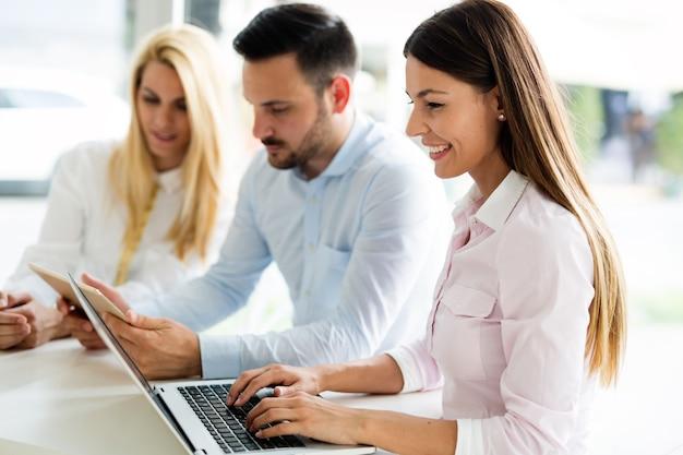 Drie jonge lachende vrolijke collega's die samenwerken aan laptop