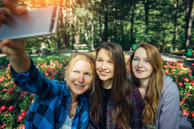 Drie jonge leuke meisjes die selfie op smartphone in de zomerpark, vriendschapsconcept nemen