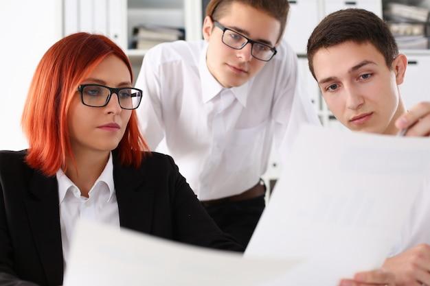 Drie jonge managers die documenten in bureau bespreken