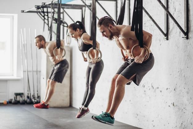Drie jonge mannelijke en vrouwelijke volwassenen doen pull-ups op ringen