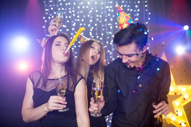 Drie jonge mannen en twee vrouwen in kappen en met glas champagne vieren een verjaardag veel plezier in een nachtclub op een feestje