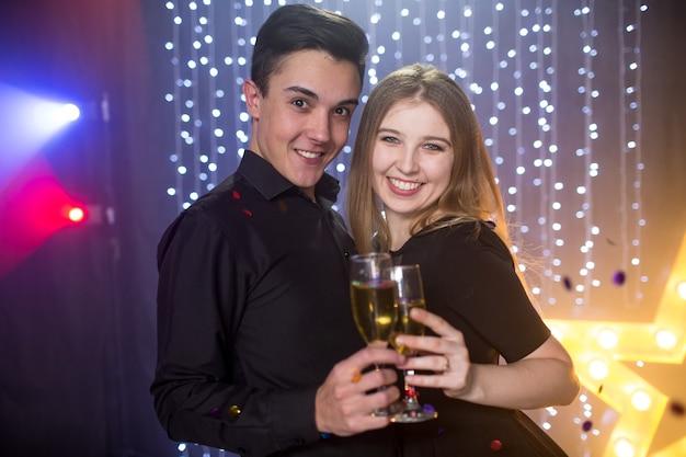 Drie jonge mannen en twee vrouwen met glas champagne vieren een verjaardag veel plezier in een nachtclub op een feestje