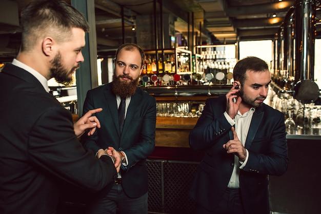 Drie jonge mannen staan in de kroeg. eén hand op koptelefoon. hij toont zijn vinger. tweede jonge man kijkt eerst en probeert te praten. derde man kijkt naar de tweede.