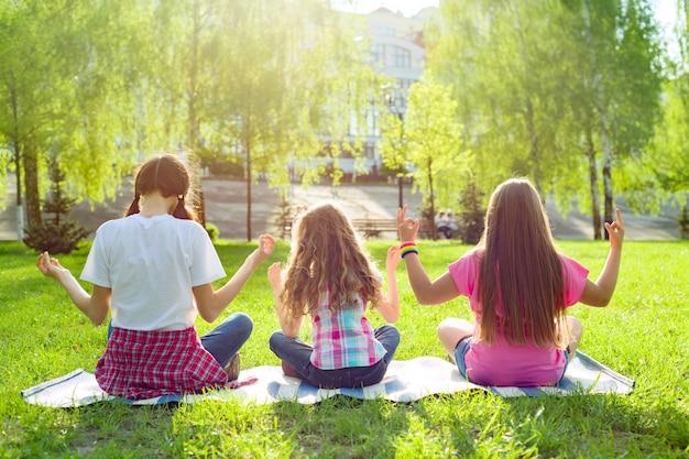 Drie jonge meisjes die yoga doen