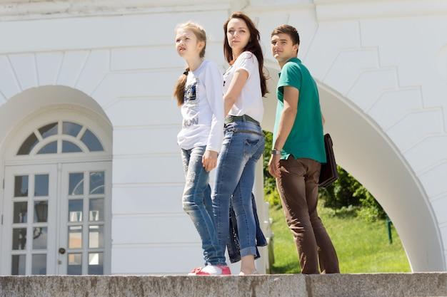 Drie jonge mensen poseren op een muur