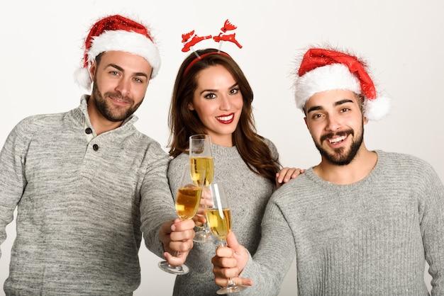 Drie jonge mensen roosteren met champagne met santa hoeden op een witte achtergrond