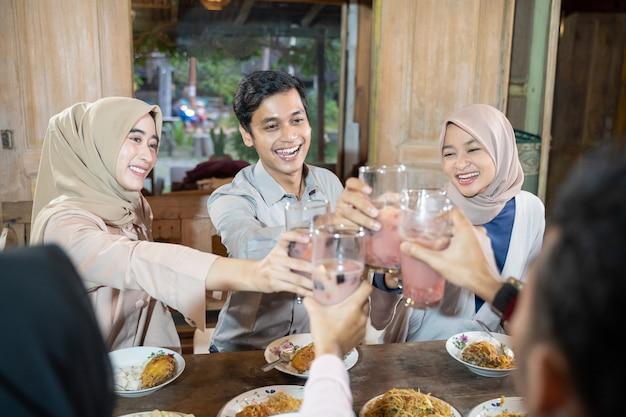 Drie jonge mensen vieren samen een glas fruitijs voor toast tijdens iftartar