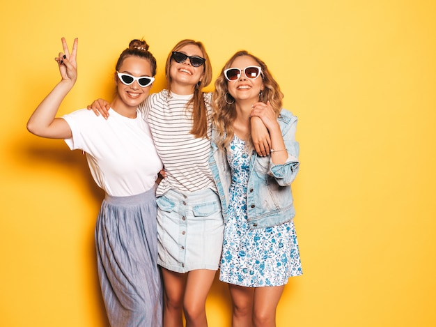 Drie jonge mooie glimlachende hipster meisjes in trendy zomerkleren. sexy onbezorgde vrouwen die dichtbij gele muur stellen. positieve modellen die plezier hebben. ze tonen vredesteken