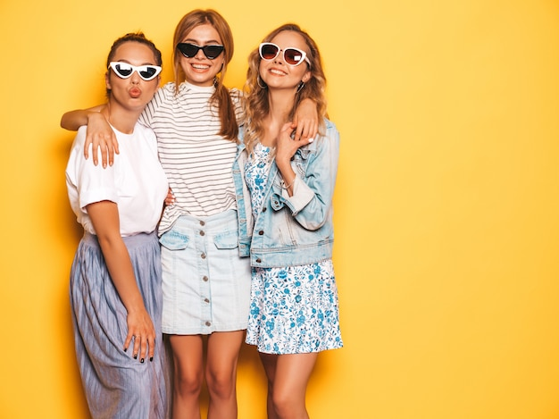 Drie jonge mooie glimlachende hipster meisjes in trendy zomerkleren. sexy onbezorgde vrouwen die dichtbij gele muur stellen. positieve modellen die pret in zonnebril hebben