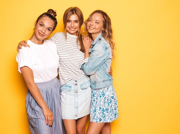 Drie jonge mooie glimlachende hipster meisjes in trendy zomerkleren. sexy onbezorgde vrouwen die dichtbij gele muur stellen. positieve modellen hebben plezier