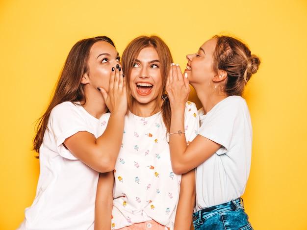Drie jonge mooie glimlachende hipster meisjes in trendy zomerkleren. sexy onbezorgde vrouwen die dichtbij gele muur stellen. positieve modellen worden gek en hebben plezier. deel geheimen, roddels