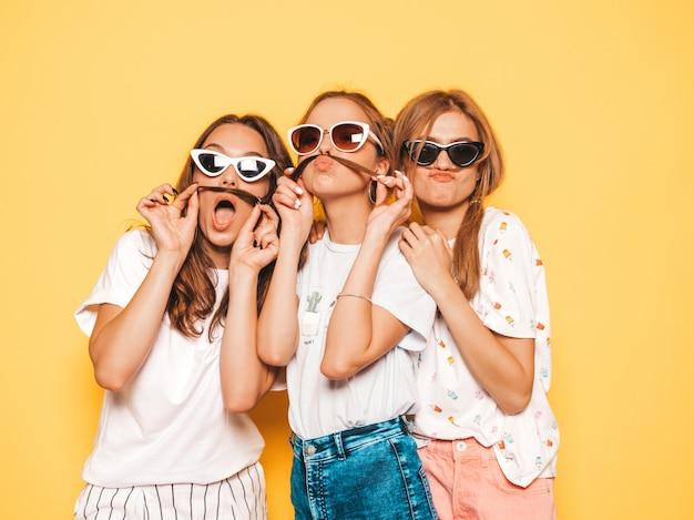 Drie jonge mooie glimlachende hipster meisjes in trendy zomerkleren. sexy onbezorgde vrouwen die dichtbij gele muur stellen. positieve modellen worden gek en hebben plezier. snor maken met haar