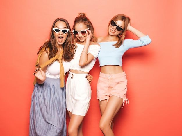 Drie jonge mooie glimlachende hipster meisjes in trendy zomerkleren. sexy onbezorgde vrouwen die dichtbij roze muur stellen. positieve modellen die pret in zonnebril hebben