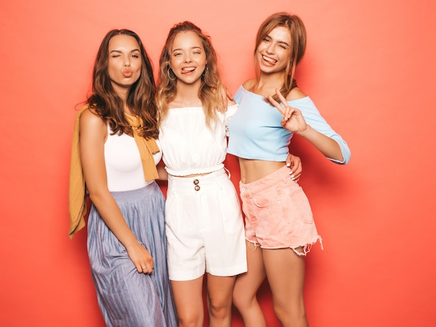 Drie jonge mooie glimlachende hipster meisjes in trendy zomerkleren. sexy onbezorgde vrouwen die dichtbij roze muur stellen. positieve modellen hebben plezier