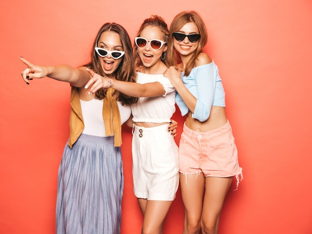 Drie jonge mooie glimlachende hipster meisjes in trendy zomerkleren. sexy onbezorgde vrouwen die dichtbij roze muur stellen. positieve modellen met plezier. aandacht voor winkelverkopen