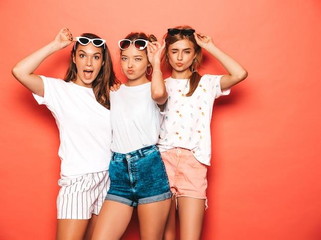 Drie jonge mooie glimlachende hipster meisjes in trendy zomerkleren. sexy onbezorgde vrouwen die dichtbij roze muur stellen. positieve modellen worden gek en hebben plezier in een zonnebril