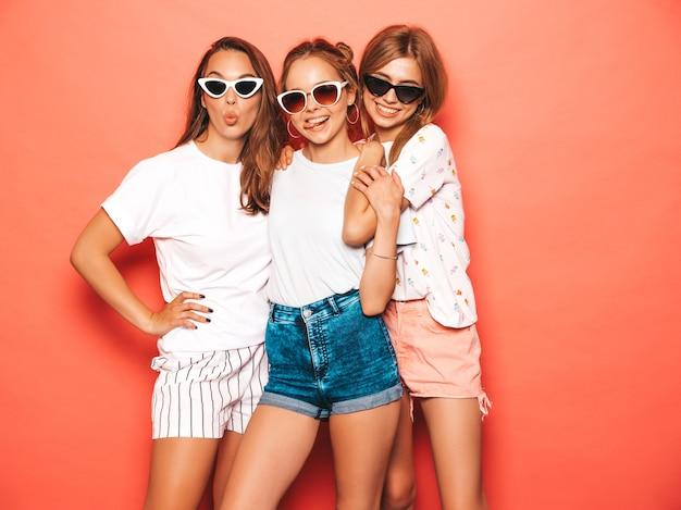 Drie jonge mooie glimlachende hipster meisjes in trendy zomerkleren. sexy onbezorgde vrouwen die dichtbij roze muur stellen. positieve modellen worden gek en hebben plezier