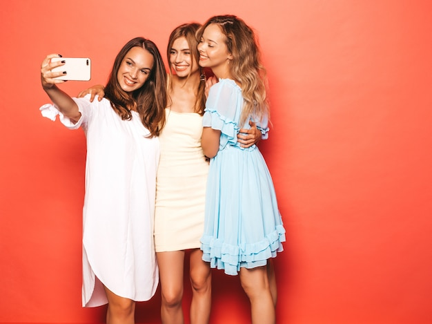 Drie jonge mooie glimlachende hipster meisjes in trendy zomerkleren. sexy onbezorgde vrouwen die dichtbij roze muur stellen. positieve modellen worden gek. zelfportretfoto's maken op smartphone