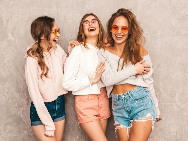 Drie jonge mooie glimlachende meisjes in trendy kleding van de de zomersport. sexy zorgeloze vrouwen poseren. positieve modellen in ronde zonnebril met plezier. knuffelen