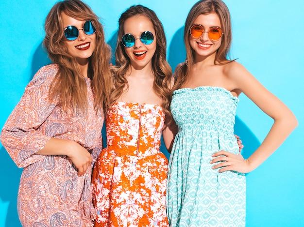 Drie jonge mooie glimlachende meisjes in trendy zomer casual jurken en in zonnebril. sexy zorgeloze vrouwen poseren.