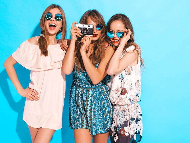 Drie jonge mooie glimlachende meisjes in trendy zomer kleurrijke jurken en zonnebrillen. sexy zorgeloze vrouwen poseren. foto's maken met een retro camera