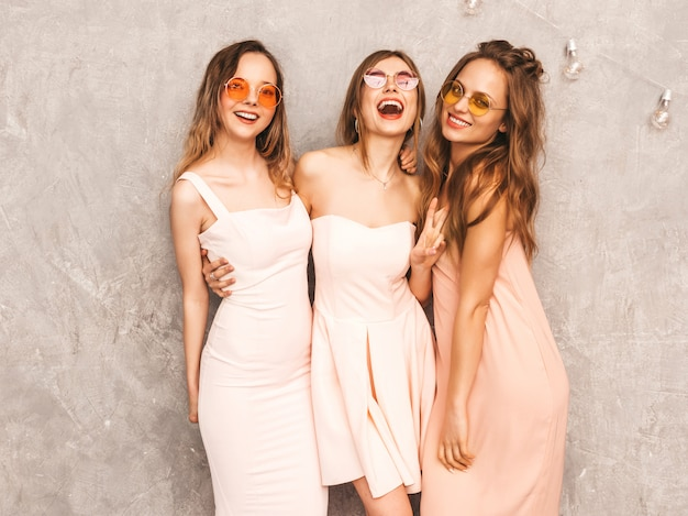 Drie jonge mooie glimlachende meisjes in trendy zomer lichtroze jurken. sexy zorgeloze vrouwen poseren. positieve modellen in ronde zonnebril met plezier
