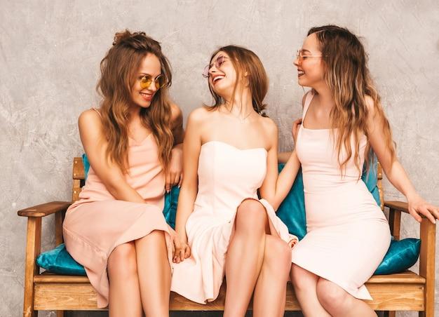 Drie jonge mooie glimlachende meisjes in trendy zomer roze jurken. sexy onbezorgde vrouwen die op bank in luxebinnenland zitten. positieve modellen in ronde zonnebril plezier hebben en communiceren