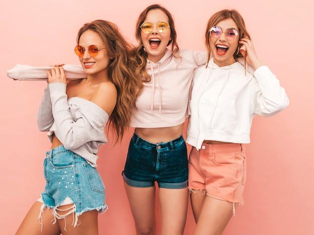 Drie jonge mooie glimlachende meisjes in trendy zomerkleren. sexy zorgeloze vrouwen poseren. positieve modellen hebben plezier