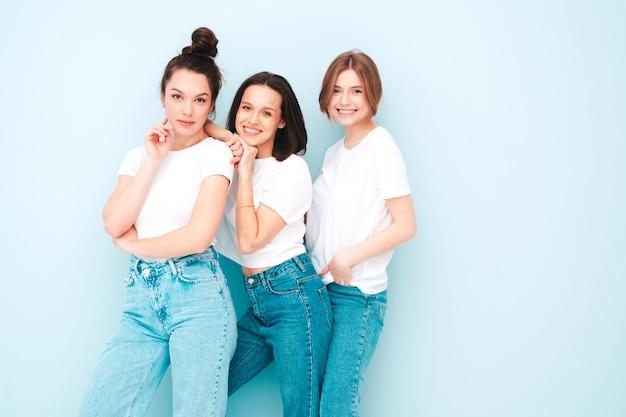 Drie jonge mooie lachende hipster-vrouwen in trendy dezelfde zomer witte t-shirt en jeans kleding