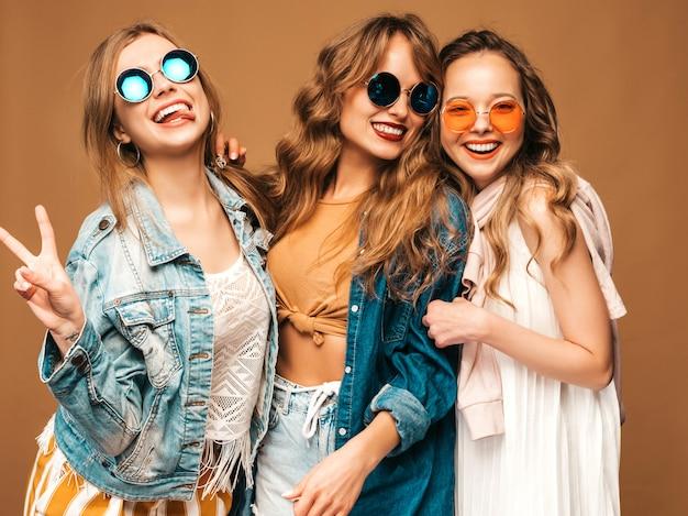 Drie jonge mooie lachende meisjes in trendy zomer casual jeans kleding. sexy zorgeloze vrouwen poseren. positieve modellen in zonnebril