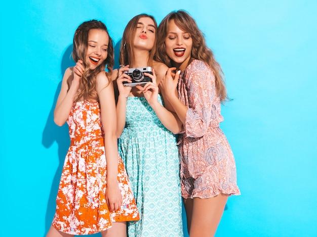 Drie jonge mooie lachende meisjes in trendy zomer casual jurken. sexy zorgeloze vrouwen poseren. foto's maken met een retro camera