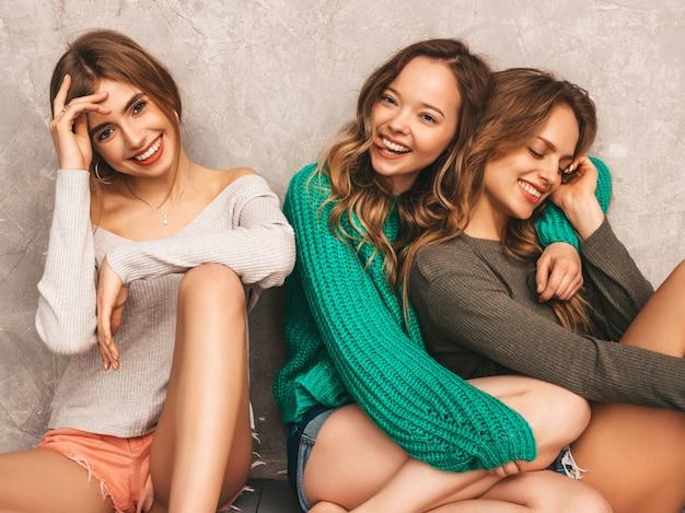 Drie jonge mooie lachende prachtige meisjes in trendy zomerkleren. sexy zorgeloze vrouwen poseren. positieve modellen hebben plezier. op de vloer zitten