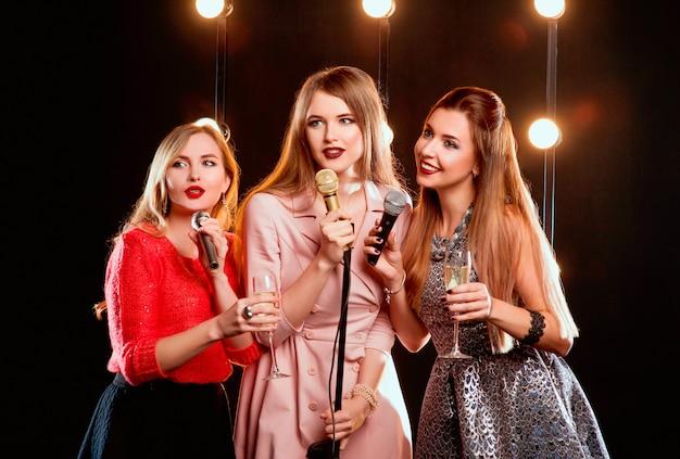 Drie jonge mooie langharige vrouwen met microfoons die liedjes zingen op het podium in karaoke