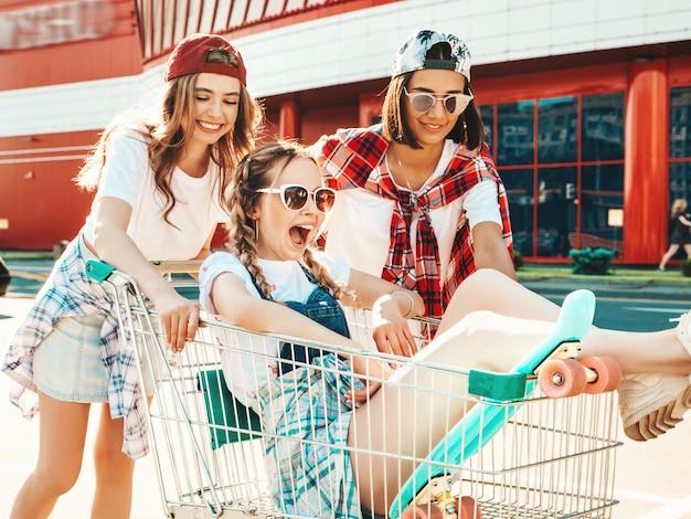 Drie jonge mooie meisjes die pret in de kruidenierswinkelkar hebben