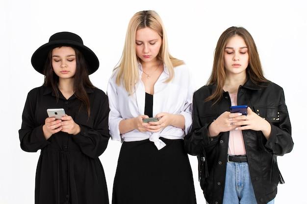Drie jonge mooie meisjes kijken naar hun smartphones. foto op een witte achtergrond