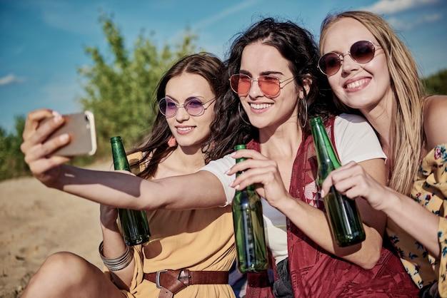 Drie jonge mooie vrouwen die een selfie maken op het strand