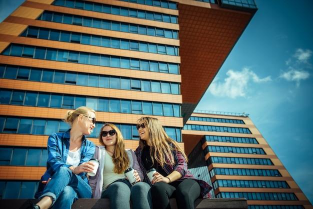 Drie jonge mooie vrouwen zitten op een bankje in een straat in de stad, drinken koffie uit een wegwerpbril, praten en lachen. vriendelijke ontmoeting buiten.